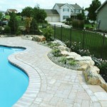 Paver patio built around the edge of swimming pool