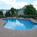 Large swimming pool surrounded by patio and flower garden