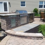 Large outdoor kitchen area with grill and built in fridge and shelves
