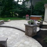 Stone columns built on edges of patio with flowers planted
