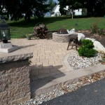 Paver patio with stone column and lantern style light fixture