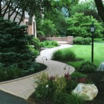 stone walkway with shrubs and landscape lighting