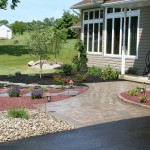 paver patio in front yard of house surrounded by plants and stone landscaping