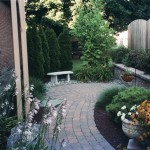 paver patio in garden area with stone bench