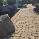 closeup of stone walkway along the edge of a flower garden