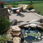 pond with surrounding stones and paver patio with lounge chairs