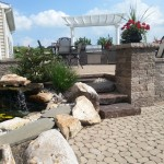 stone patio, steps, and retaining walls in backyard outdoor living space