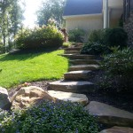 Large stone steps winding up side of hill to entrance of house