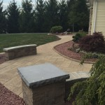 Sitting walls and on stone patio with garden planted along the edges