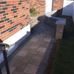 narrow paver walkway between brick house and white fence