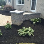 Closeup of retaining wall beside entry way with garden planted beside it