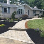 Bleached white stone walkway with curved steps leading up to front of house