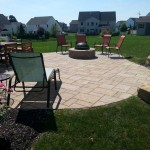 lounge chair, picnic table and fire pit on circular backyard patio