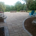 Large paver patio with stone benches and adirondack chairs