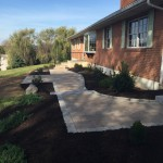 Paver patio in backyard of brick house with winding stone steps