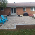 Paver patio in backyard with blue adirondack chairs and stone benches