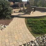 Walkway and circular paver patio in backyard with fire pit and lounge chairs