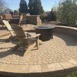 Circular fire pit installed in center of patio with chairs and sitting walls