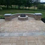 paver patio with circular fire pit and rounded sitting wall