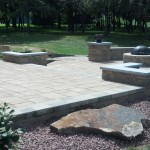 large paver patio with retaining walls and fire pit