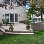 backyard patio with large retaining wall and stone steps