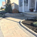 closeup of paver patio with garden bed planted along the edges
