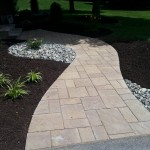 Custom cut paver walkway with mulch and stones around it