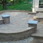 Horseshoe shaped retaining wall on backyard paver patio
