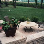 Round paver patio with lawn furniture in backyard