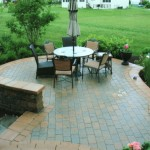 Backyard paver patio with lawn chairs around a round table