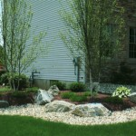 boulders and plants placed in garden on side of house