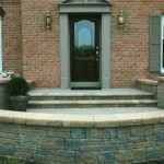 retaining wall with stone steps leading up to front door