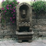 Custom lion water fountain built into retaining wall
